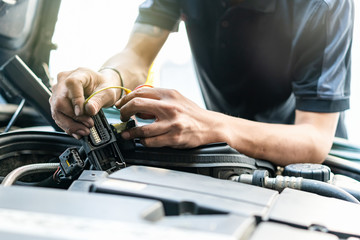 People or mechanic car repair during investigate cause of problem (electric system check) or working on automobile gasoline or diesel engine at garage