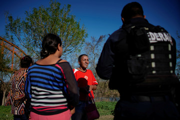 Migrants from Honduras, Nectar Sanchez and his family, are questioned by a federal police officer in Piedras Negras