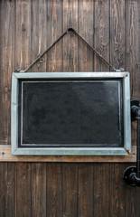 Blank rustic blackboard hanging on wooden door.