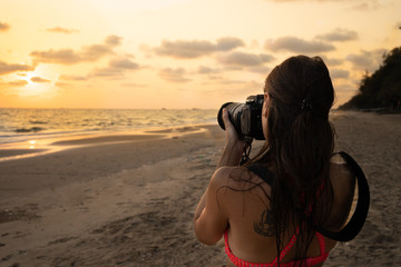woman traveler on the shore of a tropical beach photographs the sunset on camera