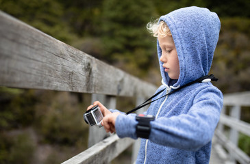 Young boy on a wooden bridge of a national park taking pictures with a action camera
