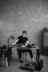 black and white photo. cute guy working with shoes, full length photo