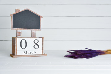 Womens day concept, happy womens day, international womens day. March 8 text wooden block calendar with purple dried flower on white wooden background.