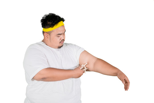 Asian fat man measures fat layer of his arm on studio