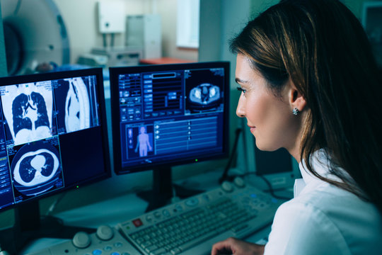 Radiologist reading a CT scan. Female doctor running CT scan from control room at hospital