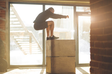 Caucasian determined sportsman performing plyometric box jumps indoor, in crossfit functional workout