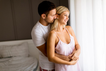 Lovely young couple standing by the window