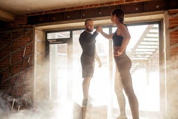 Personal fitness coach giving encouraging high five to young athletic woman, standing on plyo boxes, surrounded by dust particles