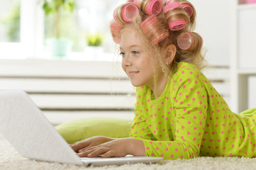Lovely little girl with pink curlers using laptop