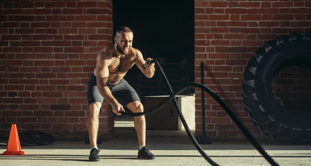Athletic young man with battle rope doing exercise in functional training fitness gym. Rope helps engage all muscle groups at the same time, while ensuring freedom of movement.