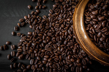 Fresh roasted arabica and robusta coffee beans. Coffee in a wooden bowl on a dark wood background