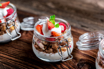 Delicious home-made muesli with yoghurt and fresh berries, beautifully presented in a mason jar to take away on the go