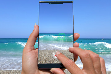 woman photographing beach with waves on a cellphone