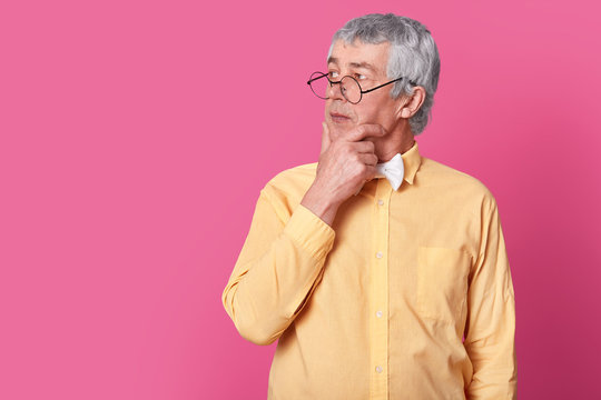 Sideways shot of old pensive grandfather looks away, holds chin, has thoughtful expression, wears spectacles, yellow shirt and bowtie, isolated over pink background with free space for your text