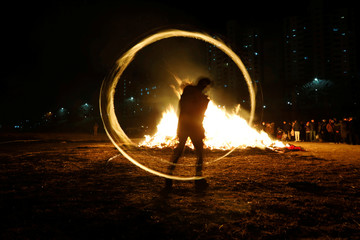 "A participant whirls a can filled with burning wood chips during a celebration ahead of ""Jeongwol Daeboreum"" (Great Full Moon), which is a traditional Korean holiday that celebrates the first full moon of the lunar calendar, at a park in Seoul"