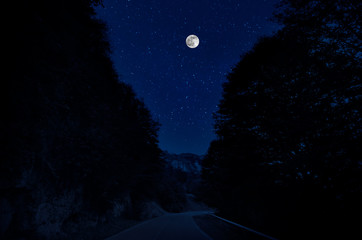 Keuken foto achterwand Nacht Mountain Road through the forest on a full moon night. Scenic night landscape of dark blue sky with moon. Azerbaijan