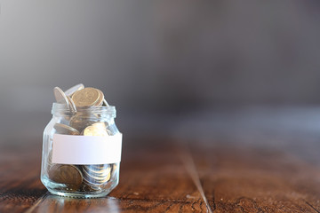 Coins in a glass jar on a wooden floor. Pocket savings from coins in the bank. Piggy bank in a glass jar with coins.