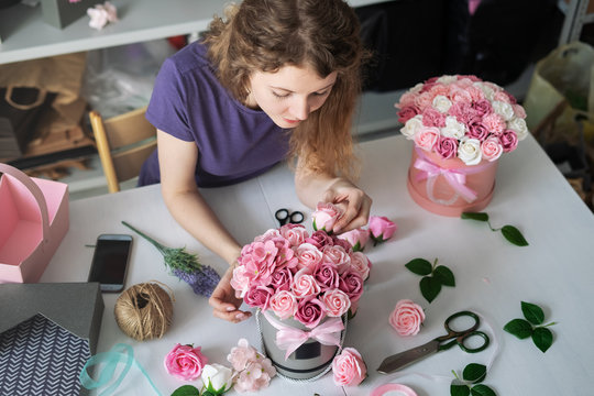 Flower shop: a florist girl collects a bouquet in a round box of pink roses. Blond curly hair, gray background.