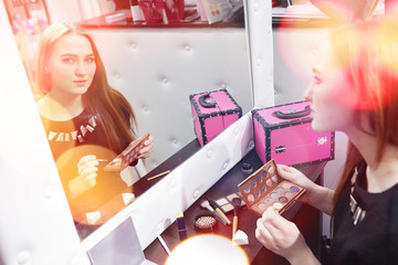 A young girl does make-up in a beauty salon. The girl in front of the mirror is making up. Beauty saloon.