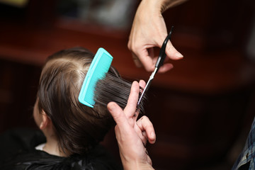 A little boy is trimmed in the hairdresser's bright emotions on face