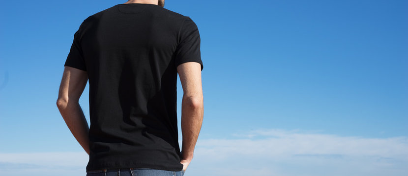 Photo of a man wearing black t-shirt. Blue sky on background