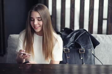 Young girl in a cafe. The girl is sitting on the couch and talking on the phone.