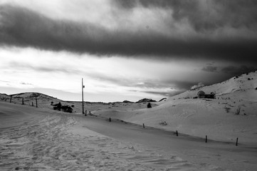 threatening sky on the top of Mount Novegno in Schio (vicenza) on a winter day. in black and white with observatory and remains of the world war