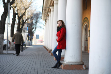 Pretty girl on a walk in red coat in the city