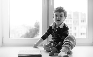 The little boy is reading a book. The child sits at the window and prepares for lessons. Boy with a book in his hands is sitting on the windowsill.
