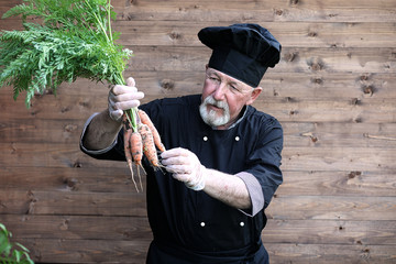 Chef senior in uniform with vegetables