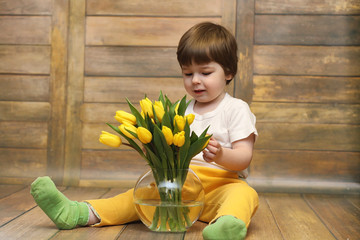 A small child with a bouquet of yellow tulips. A boy with a gift of flowers in a vase. A gift for girls on a female holiday with yellow tulips on the floor.
