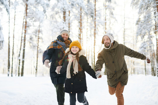 Portrait of playful family running in winter forest all smiling happily in sunlight, copy space