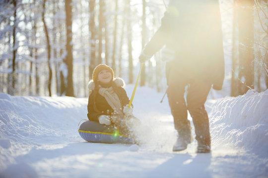 Full length portrait of happy little girl enjoying sleigh ride in winter forest lit by sunlight, copy space