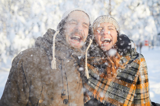Waist up portrait of excited adult couple playing with snow in winter forest  and laughing