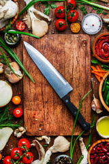 Food cooking background, ingredients for preparation vegan dishes, vegetables, roots, spices, mushrooms and herbs. Big chefs knife. Healthy food concept. Rustic wooden table background, top view