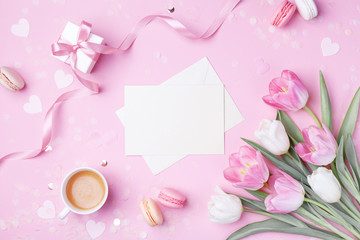 Morning cup of coffee, cake macaron, gift box, envelope and spring tulip flowers on pink background. Beautiful breakfast for Women day, Mother day. Flat lay.