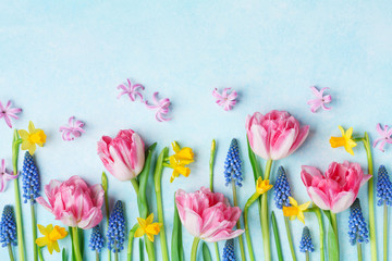 Creative composition of beautiful spring flowers on pastel table top view. Greeting card for International Women Day. Flat lay.
