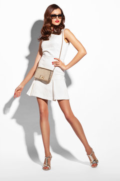 Young fashion woman in white dress and sunglasses.