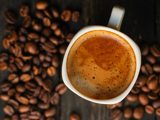 cup of hot coffee (coffee beans) - arabica and robusta blend, roasted coffee grain. Black background. Top view. Copy space