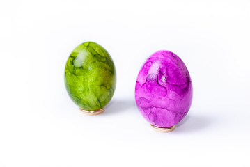 Two painted easter eggs (green and purple) standing on white background