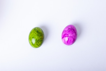 Two painted easter eggs (green and purple) laying on white background