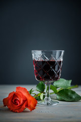 glass of red wine and rose a on a wood background