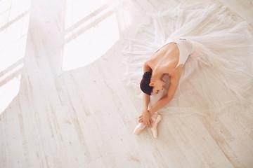 Young ballerina posing on the floor