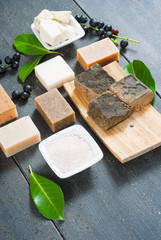 cosmetic clay, soaps, henna blocks, raw shea butter on black wood table
