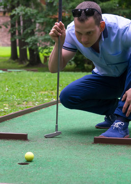 player looks at his hit on a mini golf course, close-up