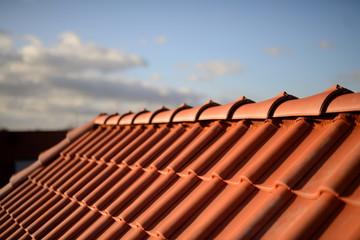 Obraz Dächer vom Dachdecker mit roten Dachziegeln. Pfannen auf Stadt Haus Neubau mit Abendrot Himmel im Hintergrund. - fototapety do salonu