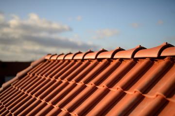 Obraz Dachfirst und glänzend rote Dachziegel Pfannen vom Dachdecker im Sonnenschein vor  dunklem Hintergrund - fototapety do salonu