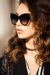 Portrait of stylish and beautiful brunette in sunglasses, with curly volumed hair after beauty salon and choker on neck. Gorgeous woman with bronze sunburn, plump lips wearing in trendy spring look.