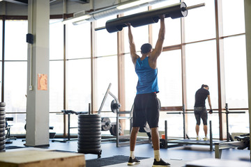 Rear view of African-american athlete standing on the floor and lifting heavy barbell while cross training in gym