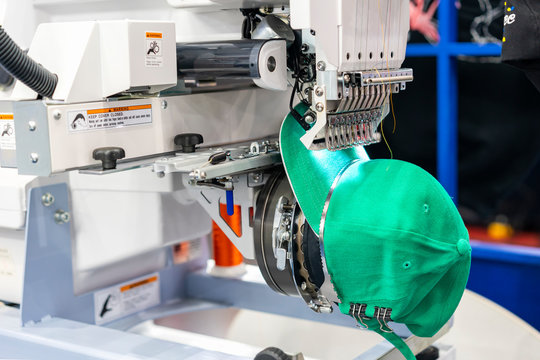 Hat sewing at modern and automatic high technology  embroidery machine for textile - clothing apparel making manufacturing process in industrial